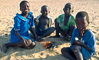 African children build fire to cook bird
