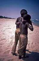 African children boys walk hugging each other on beach
