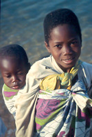 African girl carrying little sister baby on back