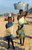 African children carry dishes on head to beach to clean